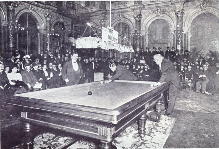"""15 januari 1906 Willie Hoppe speelt tegen Maurice """"Le Lion"""" Vignaux voor de wereldtitel kader 45/1 in de balzaal van het Grand Hotel te Parijs. Links rechtstaand de scheidsrechter Comte de Drée met de handen in de zakken."""